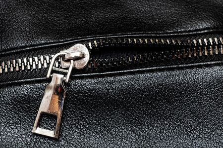 Metal clasp and zipper on leather close up Фото со стока