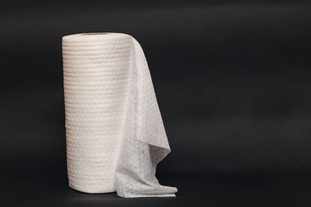Roll of fabric napkins on a black background close up