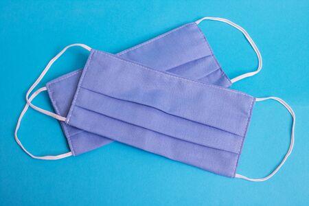 Two blue cotton medical masks on a blue background close up Reklamní fotografie
