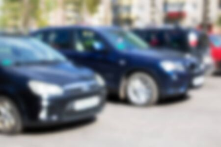 Cars parked in sunlight close up, abstract blurred background