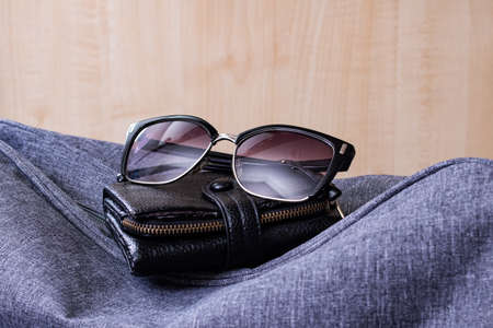Wallet, sunglasses and travel bag on a wooden background Banque d'images