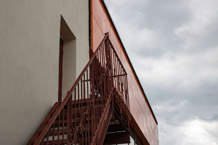 Metal staircase to roof of building on gloomy sky Archivio Fotografico