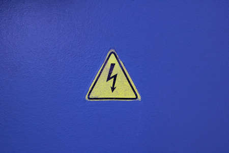Yellow electricity sign on a blue wall close up