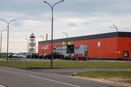 BELARUS, POSTAVY - JULY 7, 2020: Large supermarket and parking for cars at sunset