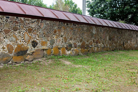 Old stone wall with green garden close up