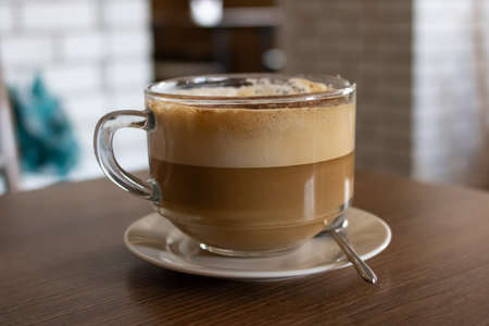 Large glass mug with coffee with milk close up