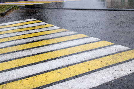 Raindrops on asphalt and pedestrian crossing close up, background