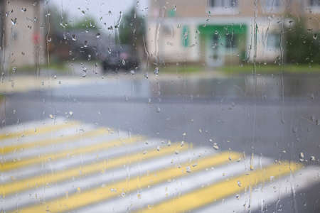 Raindrops on glass against the background of the city