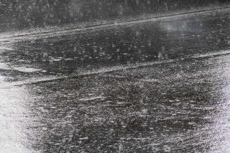 Raindrops on asphalt closeup, background or texture
