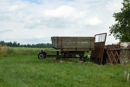 Old tractor trailer in the field closeup