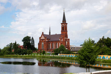 Red brick church by river and cloudy sky 스톡 콘텐츠