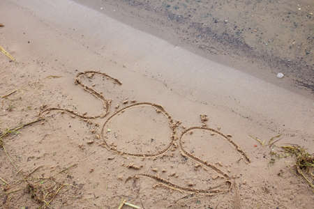 SOS letters in the sand on the beach close up