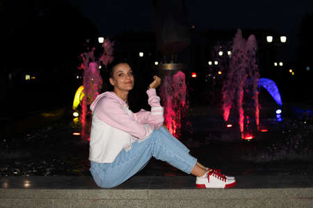 Young smiling girl sits at the fountain at night