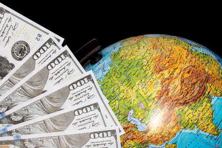 Dollar bills and globe on a black background