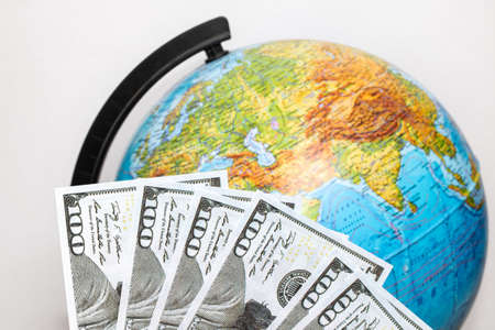 Dollar bills and globe on a white background