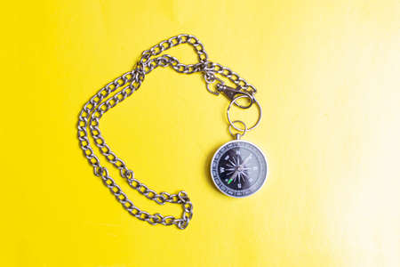 Compass with chain on a yellow background close up