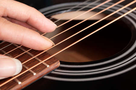 Fingers on the strings of a black guitar close up Stock Photo