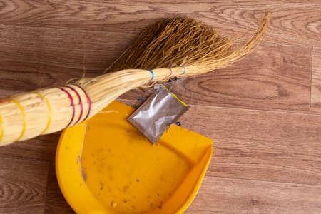 Broom and scoop removes garbage on wooden floor close up Foto de archivo