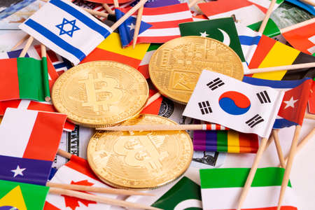 Bitcoins coin on the background of flags of different countries close up Zdjęcie Seryjne