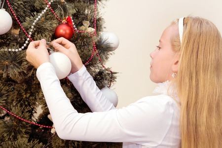 waiting glance: Blond little girl decorates a Christmas tree at home