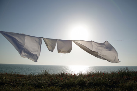 linens dries in the fresh air on a background the sea and sunset