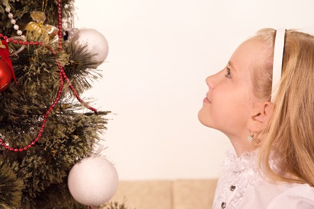 Little girl looking at the top of the Christmas Tree.