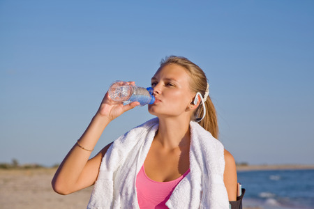 fitness athletic young woman on beach drinking water after exercise