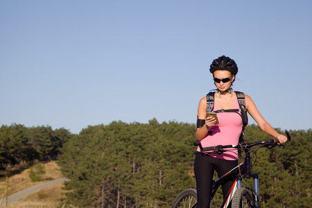 athletic young woman on a mountain bike with a phone in his hand Stock Photo