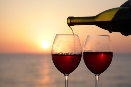 burgundy drink glass: Two glasses of red wine at sunset