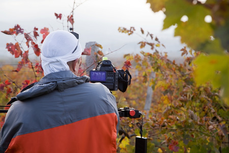 Videographer on a vineyard in autumn shoots video
