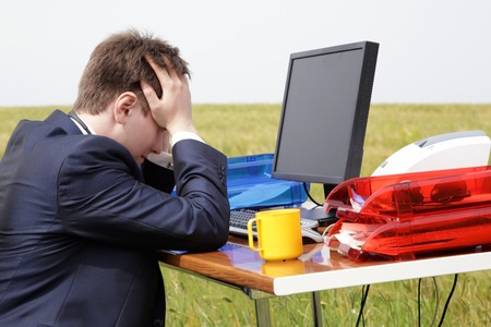 Businessman with a headache from work sitting at a desk in a field Stock Photo