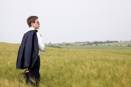 Aspiring businessman standing in a field thinking about starting a business Stock Photo