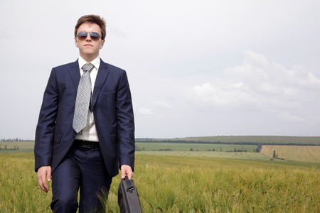 Businessman in a suit goes along the field thinking about work