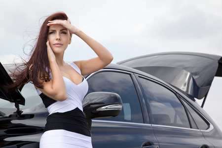 Young woman near the car talking on the phone while waiting for aid