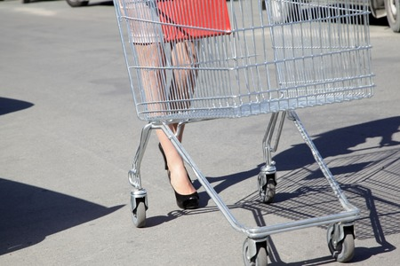 Young girl goes to the supermarket with a wheelbarrow for products