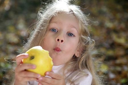 Adorable little girl funny eating yellow apple