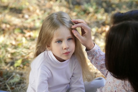 Mom gently stroking her daughters head sitting in autumn park Stock Photo