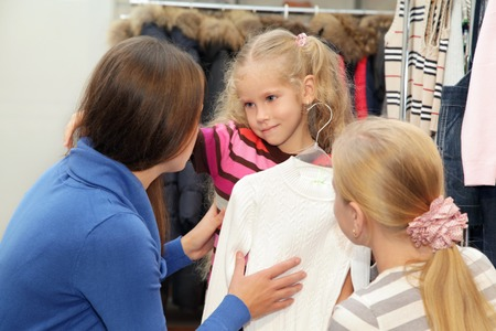 Mom in clothes shop tries on sweater to a daughter
