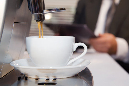 Businessman prepares espresso by means coffee machine