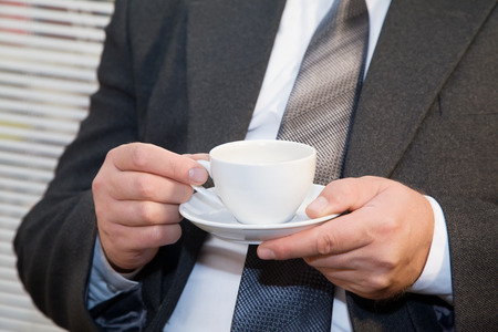 Male businessman in the office with a cup of coffee in hands