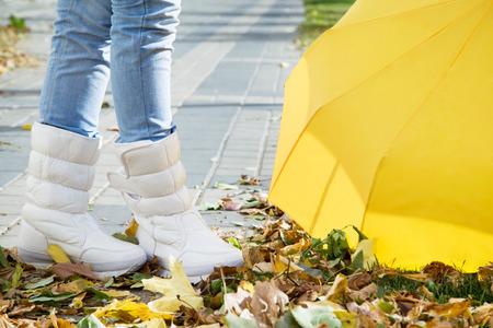 Legs in boots with umbrella  autumn street closeup Stock Photo