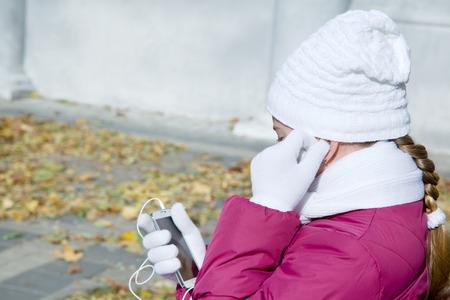 Girl child adjusts earphones talk on a cell autumn outdoors