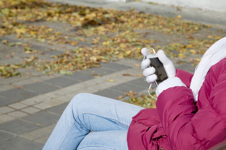 Mobile with headphones in hands at the girl sitting on a bench in the city Stock Photo