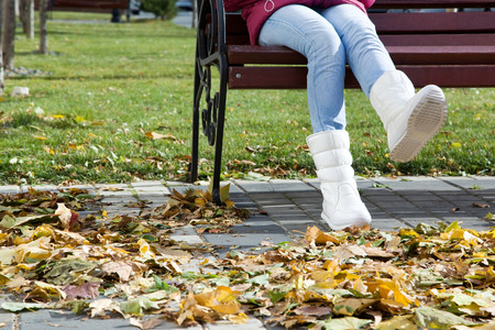 Girl sitting on a bench in autumn city cheerfully waving legs