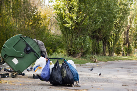 homeless hunger makes feed on from the container with garbage Stock Photo