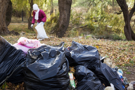 bags of garbage are in park polluting the environment Stock Photo