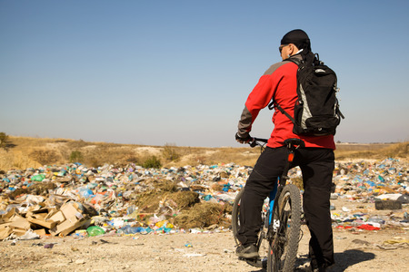 Adult man on a bicycle stayed having seen landfill