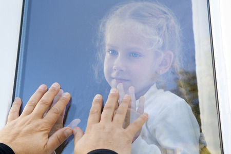 Little girl touching the hands of his father is forgiven through the window