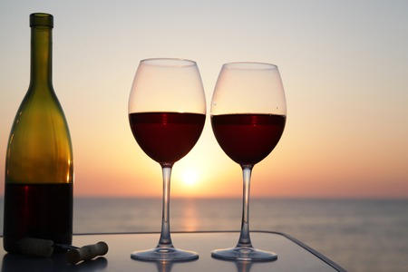Bottle of wine with wine glasses at sunset on the sea background