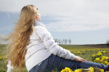 girl  blond sitting in a field with yellow flowers raised her head to the sunlight